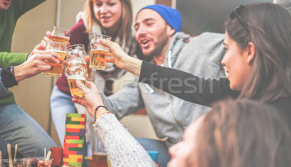 Happy friends cheering with beer and playing board games in bar  Stock photo © DisobeyArt