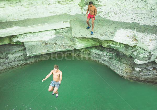 Jonge vrienden springen rivier reizen vriendschap Stockfoto © DisobeyArt