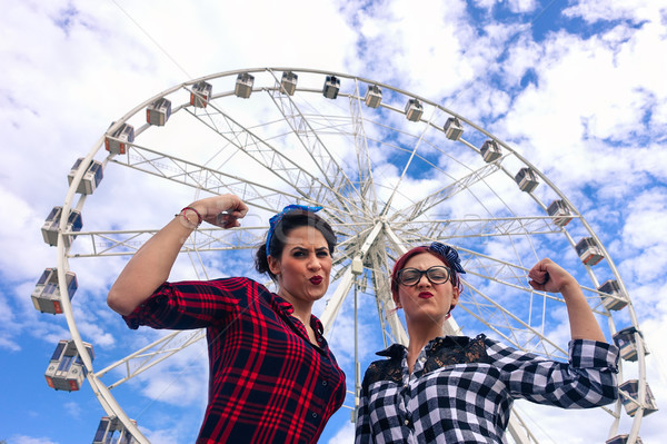Pin up friends making funny gym position in front of ferris whee Stock photo © DisobeyArt