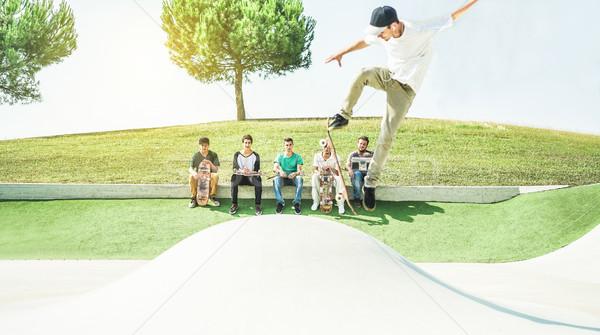 Jonge skater springen skateboard vrienden kijken Stockfoto © DisobeyArt