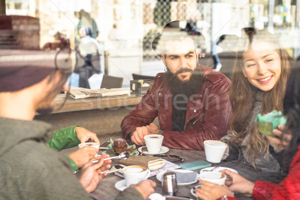 Group of friends enjoying cappuccino and latte macchiato togethe Stock photo © DisobeyArt