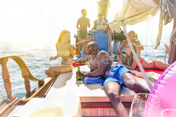 Group of multiracial friends chilling and drinking beers in boat Stock photo © DisobeyArt
