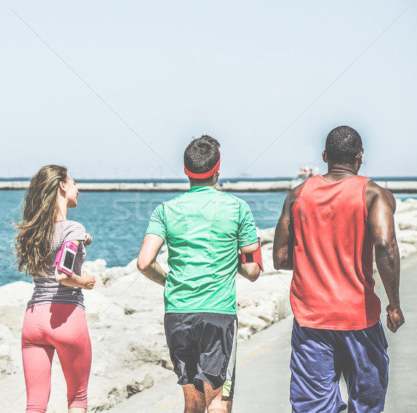 Young diverse culture joggers running next to the sea harbor - R Stock photo © DisobeyArt