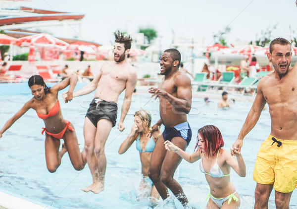 Group of multiracial friends jumping inside swimming pool in aqu Stock photo © DisobeyArt