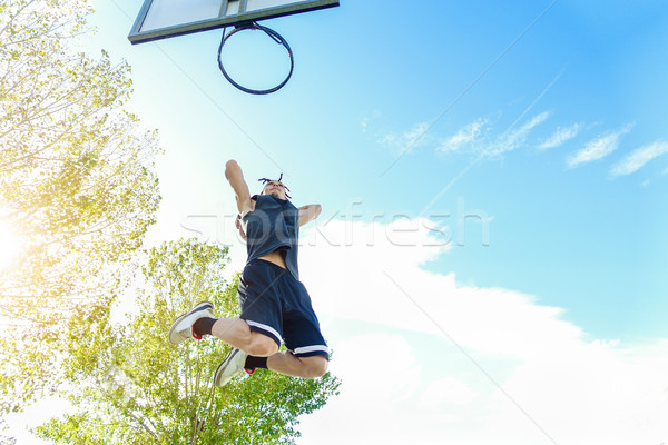 Young dreadlocks player dunking in urban city basketball court w Stock photo © DisobeyArt