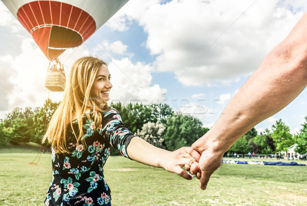Happy young woman wants to make balloon tour holding boyfriend's Stock photo © DisobeyArt