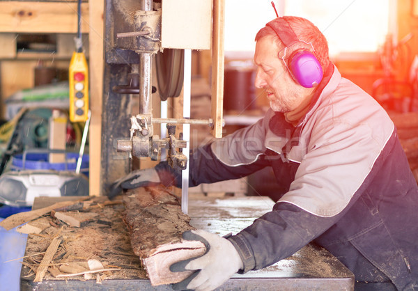 Strong man carpenter using table saw for cutting wood at worksho Stock photo © DisobeyArt
