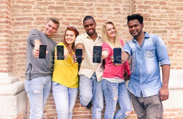 Csoport barátok mutat okostelefon kint fiatal Stock fotó © DisobeyArt
