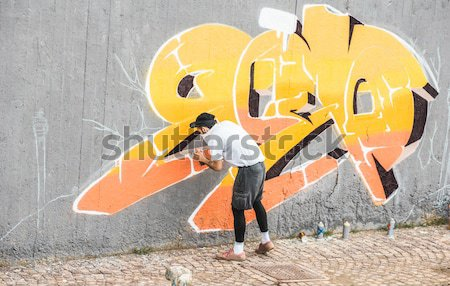 Graffiti artist covering his face while painting with color spra Stock photo © DisobeyArt