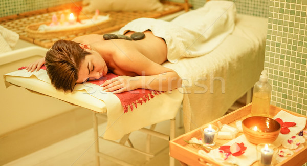 Young woman having hot stone therapy massage in spa hotel resort Stock photo © DisobeyArt