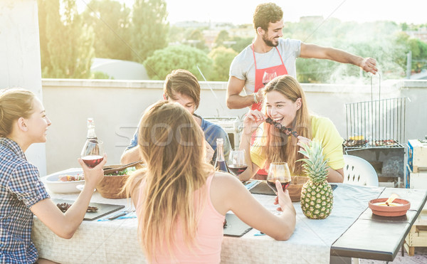 Young friends eating and drinking red wine at rooftop barbecue p Stock photo © DisobeyArt