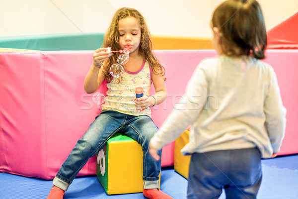 Two little female children blowing soap bubbles in playground nu Stock photo © DisobeyArt