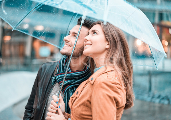 Young happy couple under the rain day covering with transparent  Stock photo © DisobeyArt