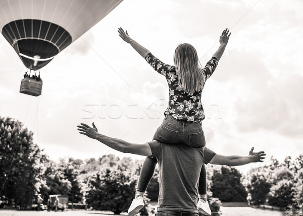 Happy freedom couple making piggyback with open arms in front ba Stock photo © DisobeyArt