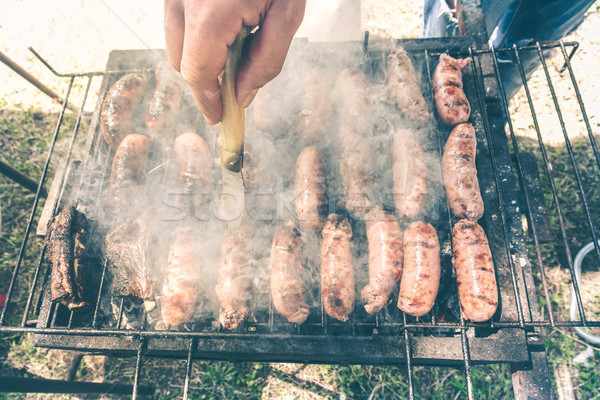 Young man cooking meat on barbecue - Chef putting some pork saus Stock photo © DisobeyArt