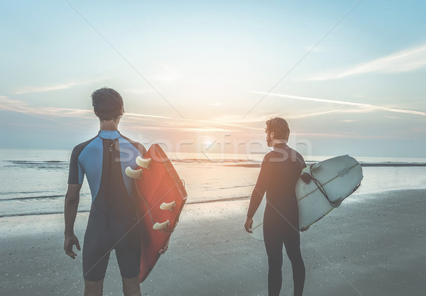 Young surfers waiting the waves on beach with sun light in backg Stock photo © DisobeyArt