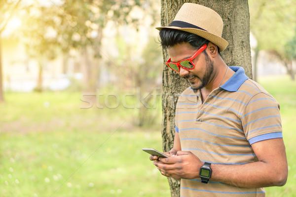 Mutlu Hint adam bakıyor cep telefonu gülen Stok fotoğraf © DisobeyArt