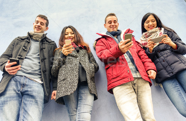 Csoport fiatal barátok néz okostelefonok óváros Stock fotó © DisobeyArt