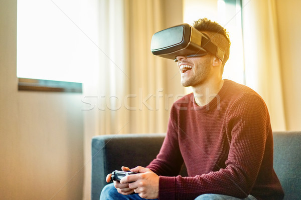 Happy gamer man playing video games virtual reality glasses in h Stock photo © DisobeyArt