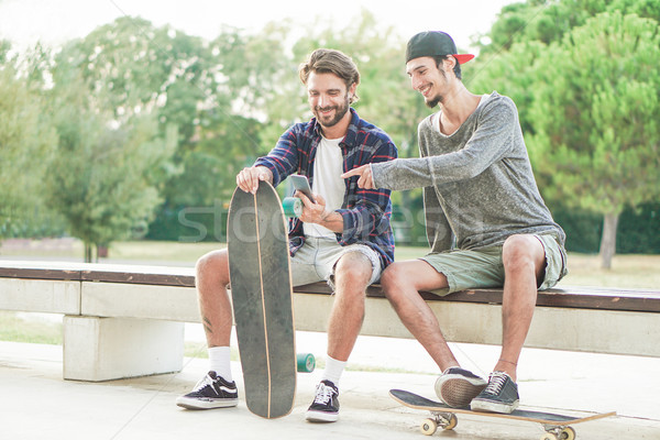 Happy skaters having fun watching videos in smartphone at city p Stock photo © DisobeyArt