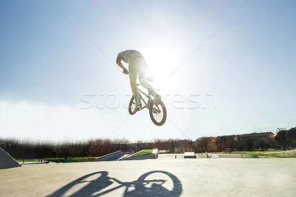 Bmx biker jumping against the sun in city skate park outdoor - Y Stock photo © DisobeyArt