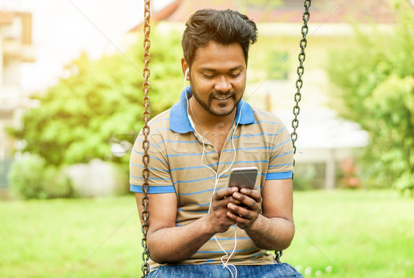 Happy young Indian man watching videos and sharing with mobile c Stock photo © DisobeyArt