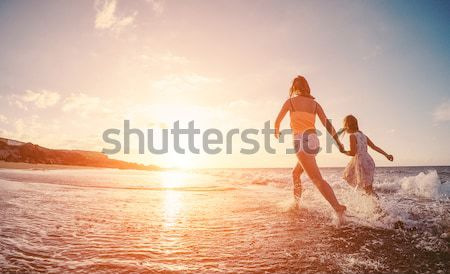 Young couple in love kissing on the beach at sunset - Two lovers Stock photo © DisobeyArt