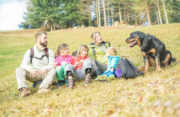 Stock photo: Happy traveler family sitting on grass with dog after trekking i