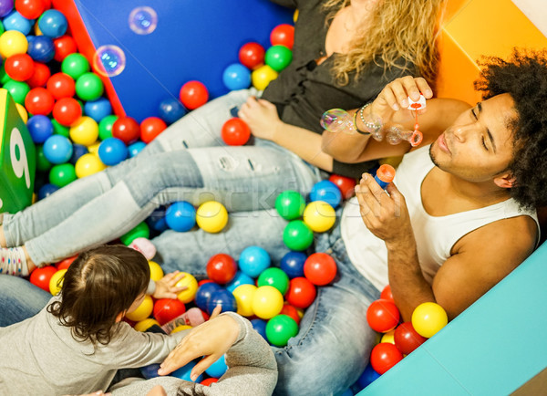 Multi ethnic parents playing with daughter inside ball pit swimm Stock photo © DisobeyArt