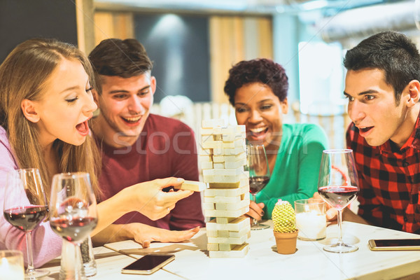 Group of young friends having fun playing board game in pub wine Stock photo © DisobeyArt