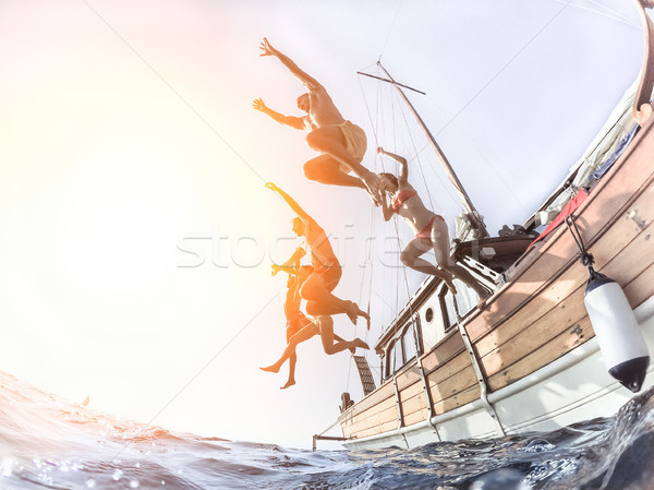 Stock photo: Multiracial young people diving from sailing boat into the sea -