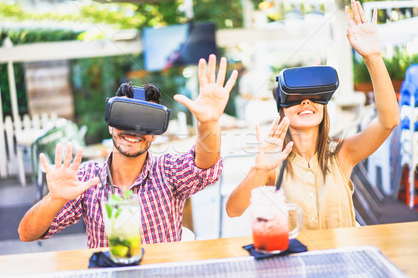Amazed friends looking in VR goggles and gesturing with hands in Stock photo © DisobeyArt