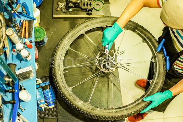 Top view of stylish bicycle mechanic working in mountain bike sh Stock photo © DisobeyArt
