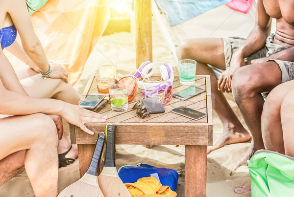 Group of multiracial friends drinking and relaxing under sun umb Stock photo © DisobeyArt