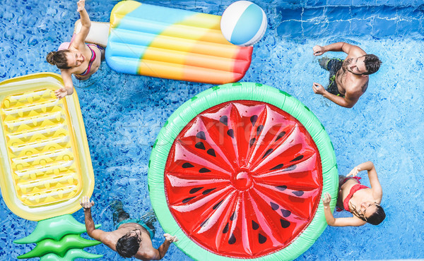 Stock photo: Happy friends playing with ball inside swimming pool - Young peo