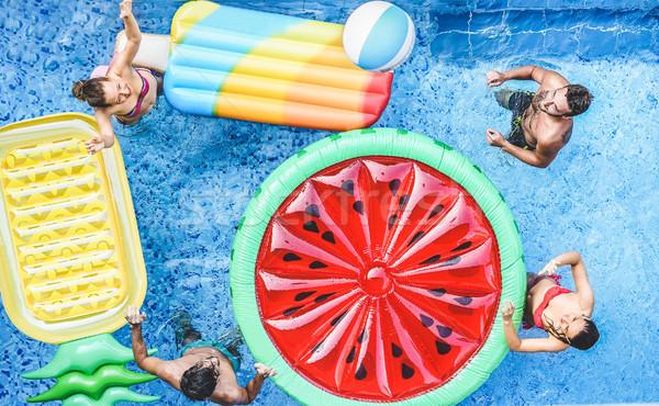 Szczęśliwy znajomych gry piłka wewnątrz basen Zdjęcia stock © DisobeyArt