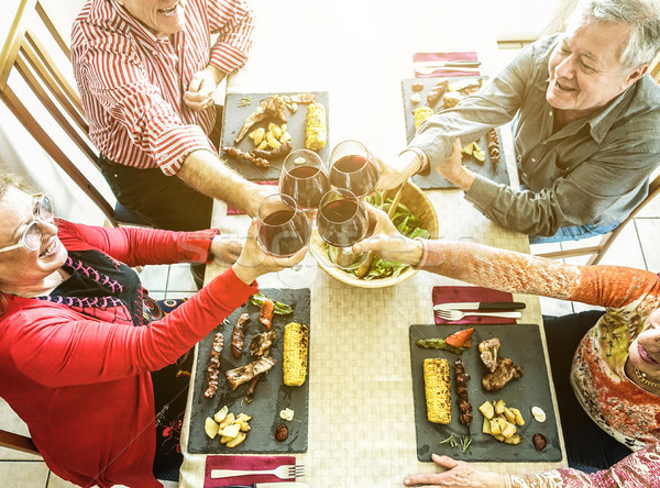 Stock photo: Happy senior friends toasting with red wine at bbq lunch - Old p