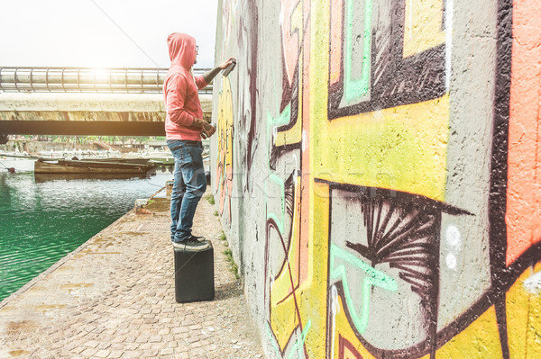 Tattoo graffiti writer painting with color spray his dark pictur Stock photo © DisobeyArt