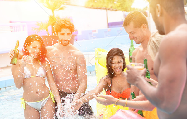 Group of multi ethnic friends having party in pool drinking cock Stock photo © DisobeyArt