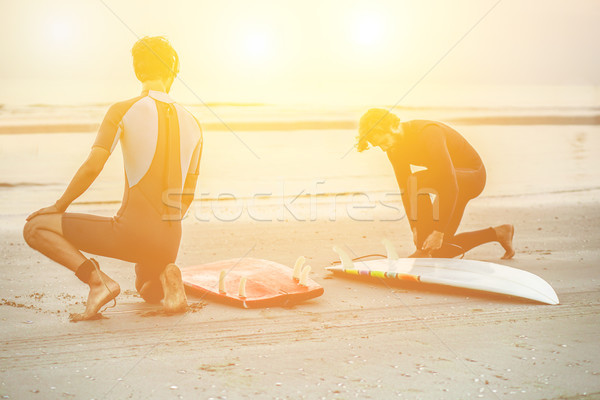 Two silhouette friends wearing swimwear with surfboards on beach Stock photo © DisobeyArt
