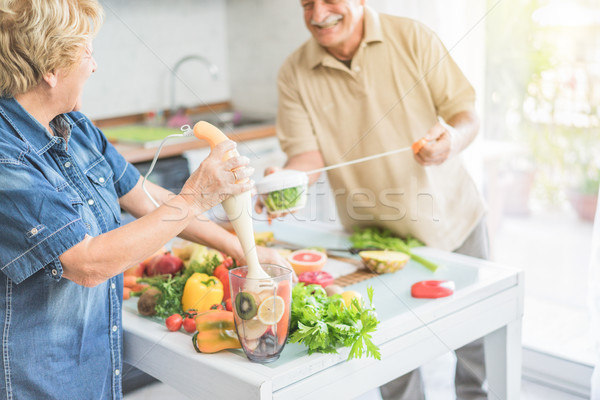 Senior couple cooking healthy vegan meal with fruits and vegetab Stock photo © DisobeyArt