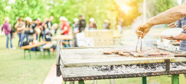 Man cooking bbq meat at festival outdoor - Chef grilling sausage Stock photo © DisobeyArt