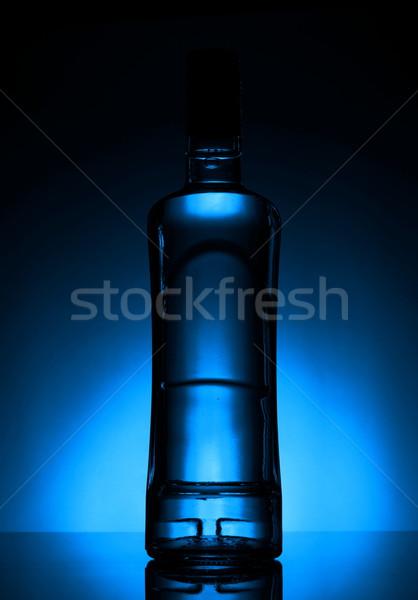 Bottle of vodka lit with blue backlight Stock photo © dla4