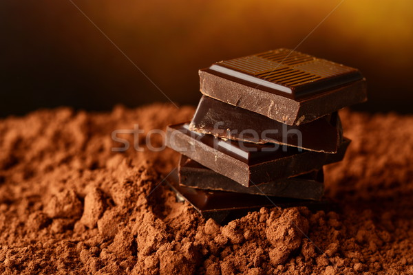 Heap of blocks of chocolate on cocoa powder Stock photo © dla4