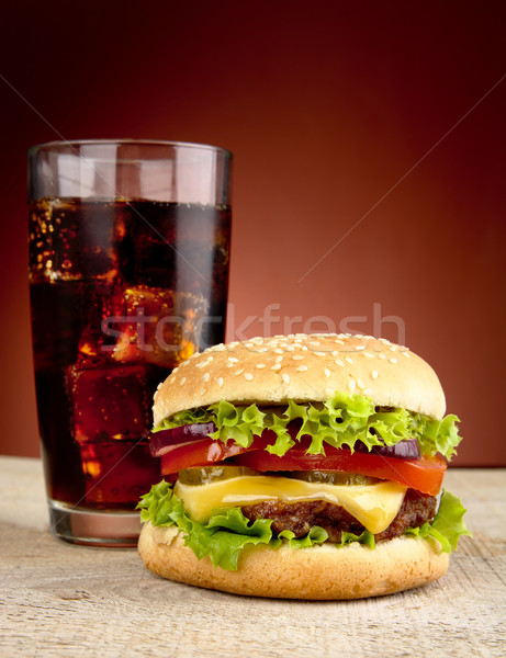 Stock photo: Big cheeseburger with glass of cola on wooden table