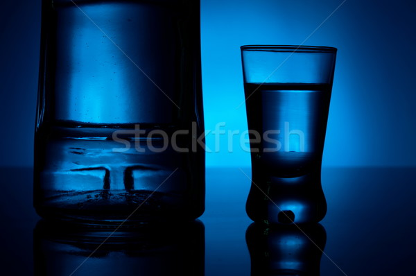 Bottle of vodka with glass lit with blue backlight Stock photo © dla4