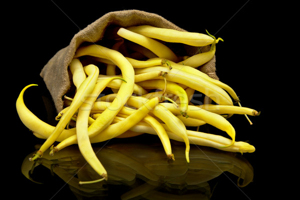 Stack of yellow beans in linen sack on black Stock photo © dla4