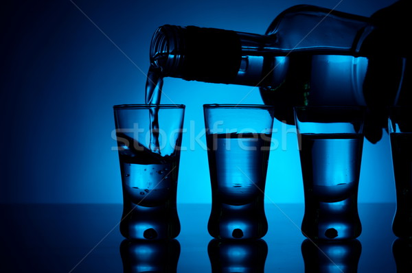 Vodka poured into a glass with glasses lit with blue backlight Stock photo © dla4