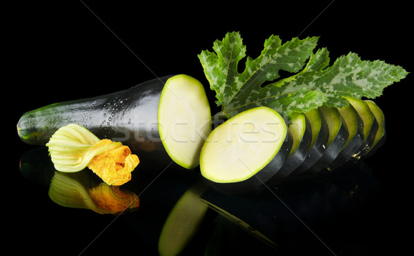 Dewed zucchini cut into slices with flower and leaf on black Stock photo © dla4