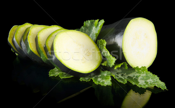 Courgettes cut into slices and leaves on black Stock photo © dla4